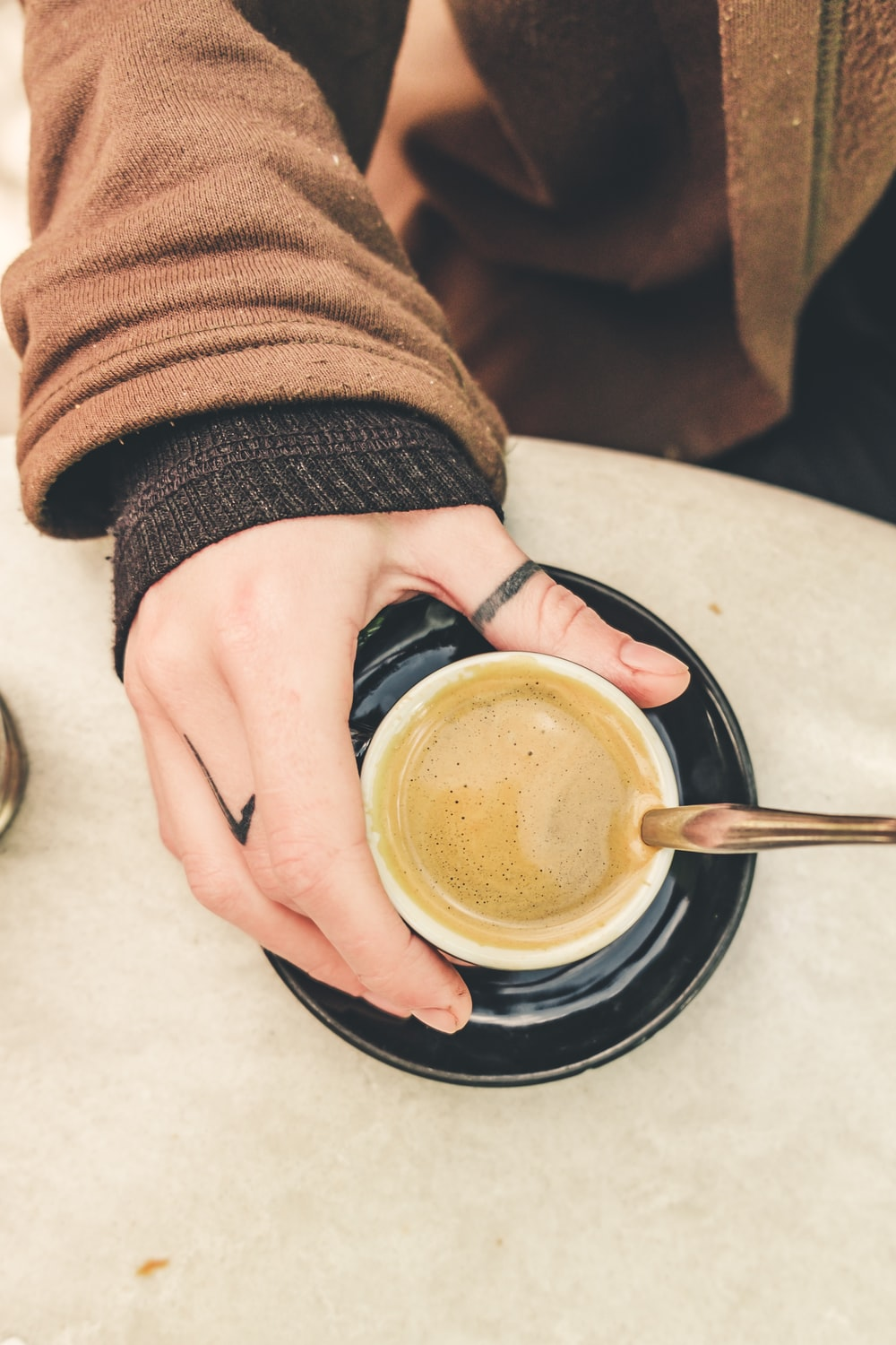 person holds cup of cappuccino on table