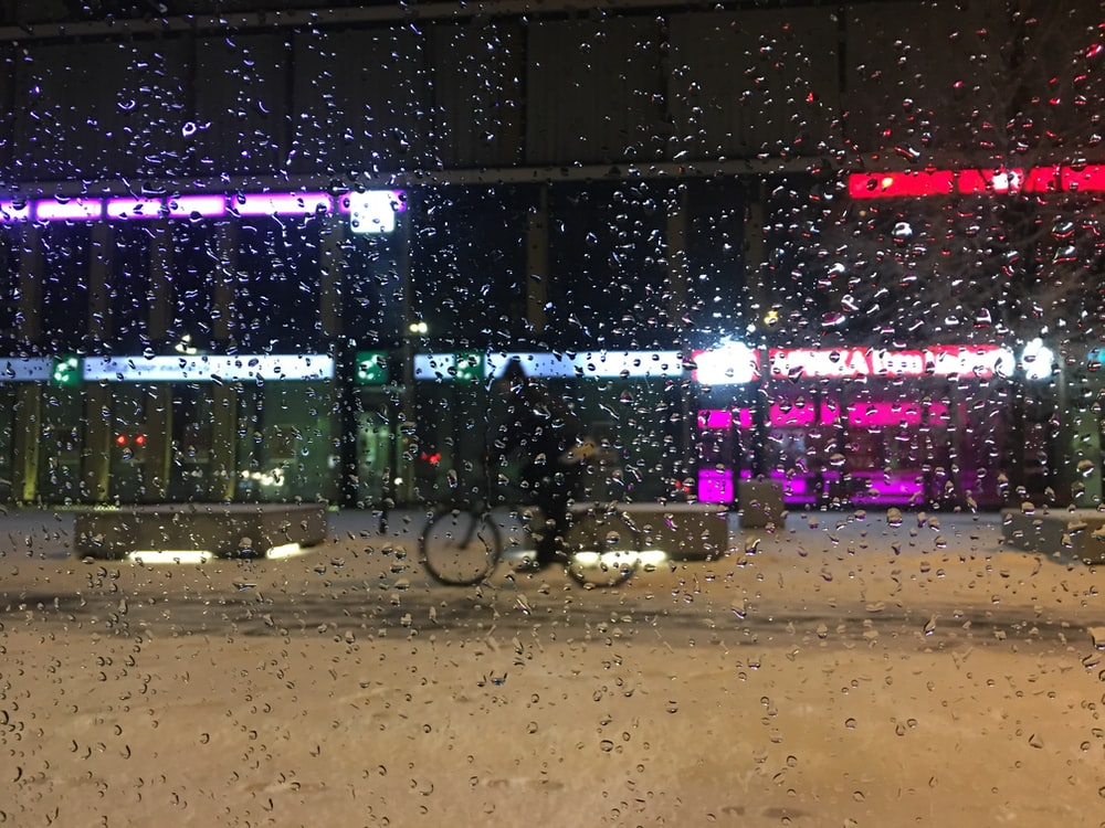 man riding bike on snow covered road at night time