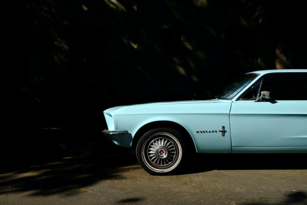 teal classic Ford Mustang parked on side of road