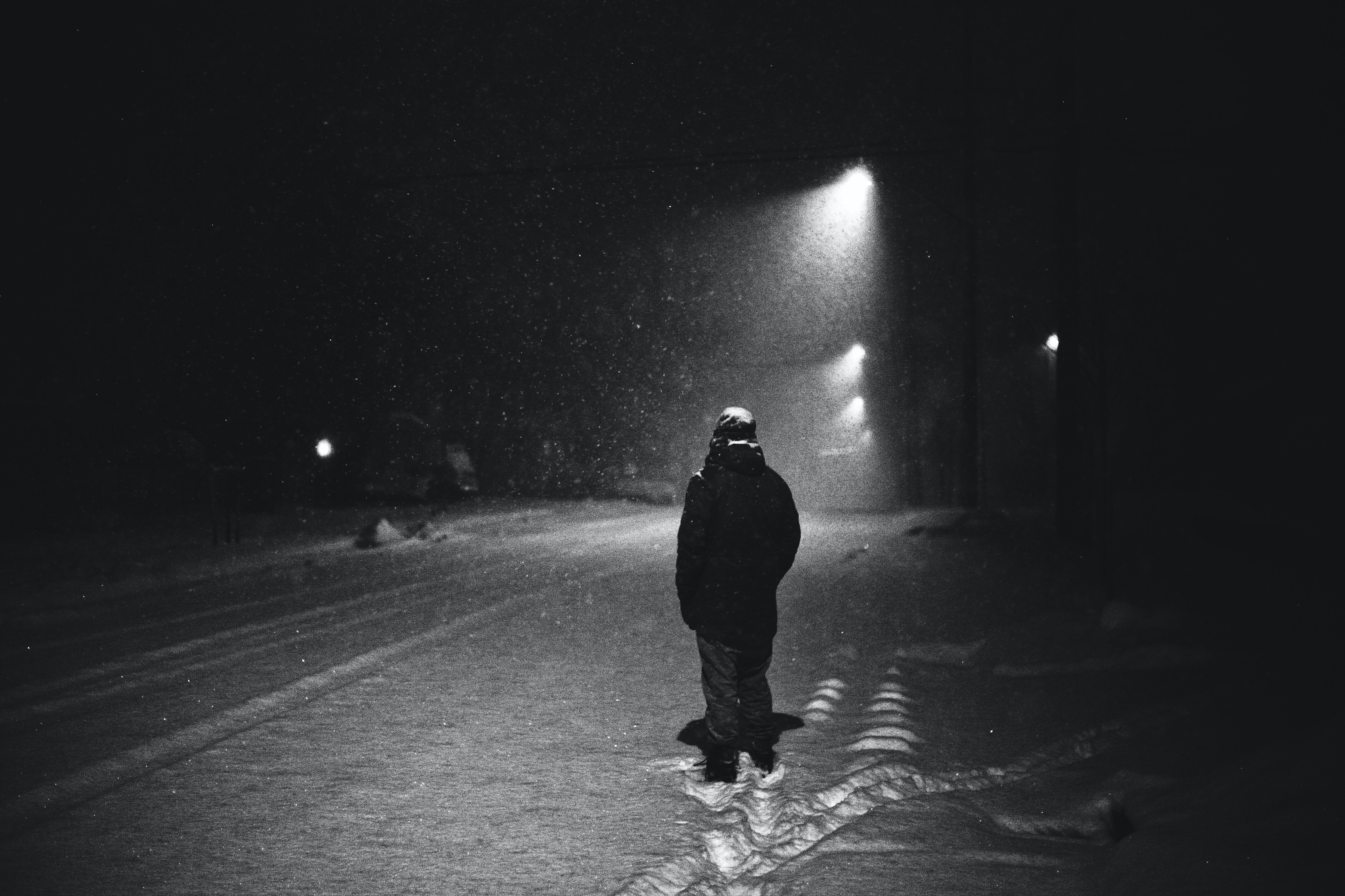 grayscale photography of man standing on street