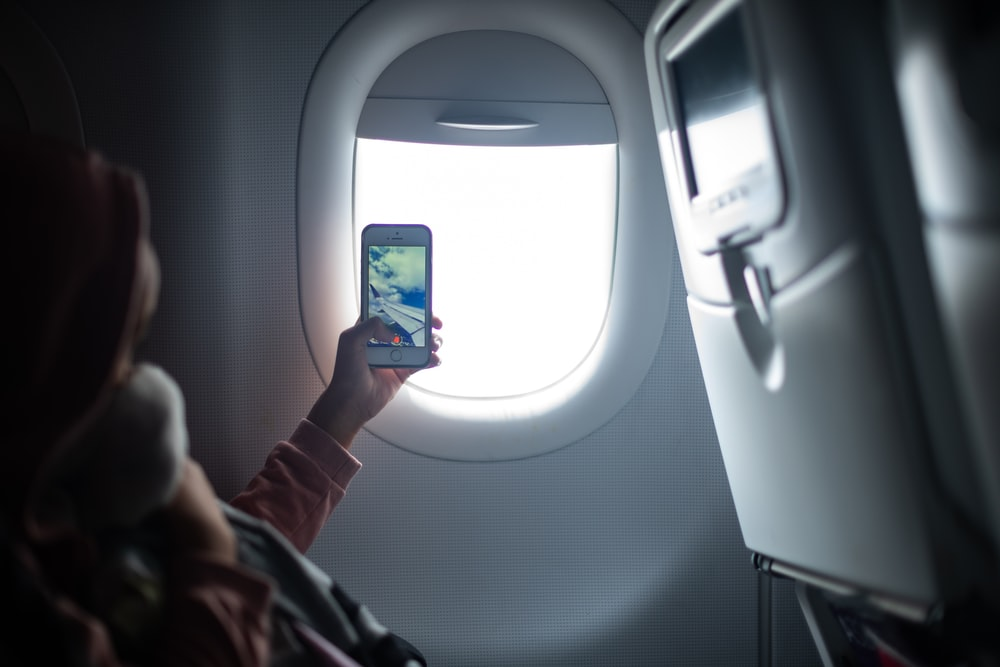 woman holding iPhone taking photo inside airplane