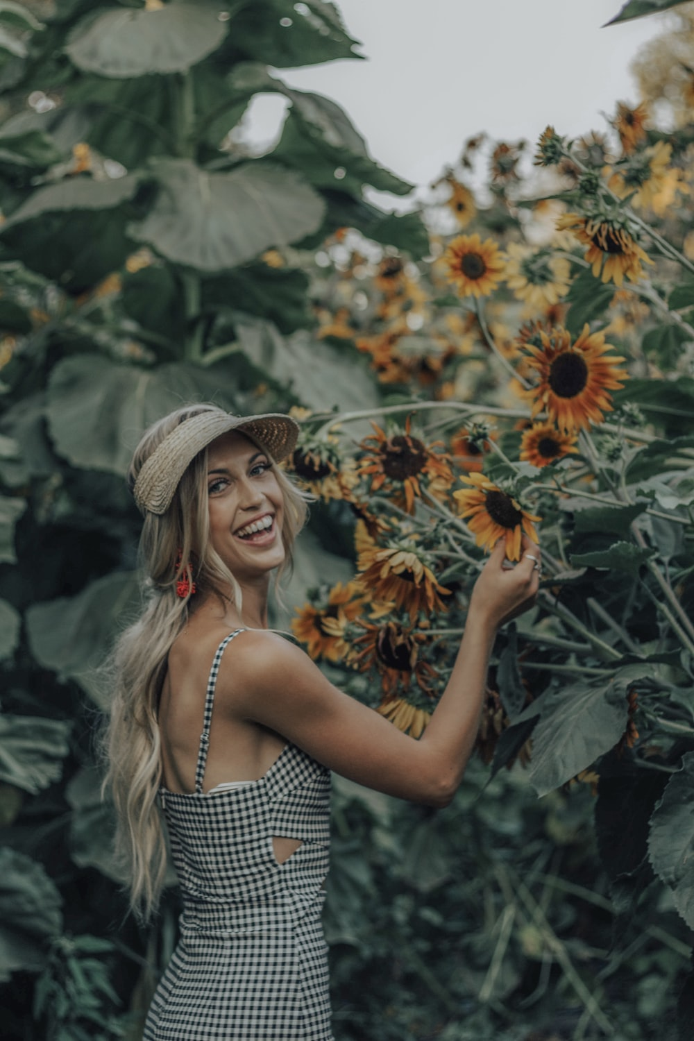one unknown celebrity smiling while holding sunflower