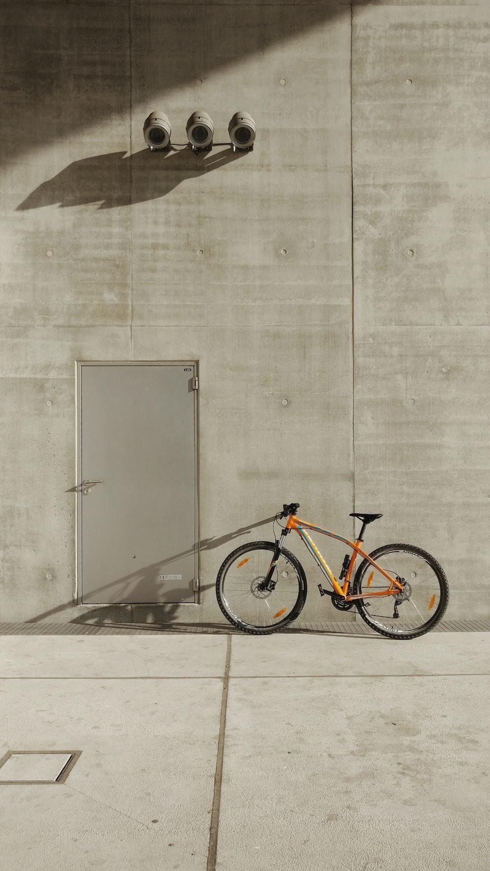 orange mountain bike beside wall