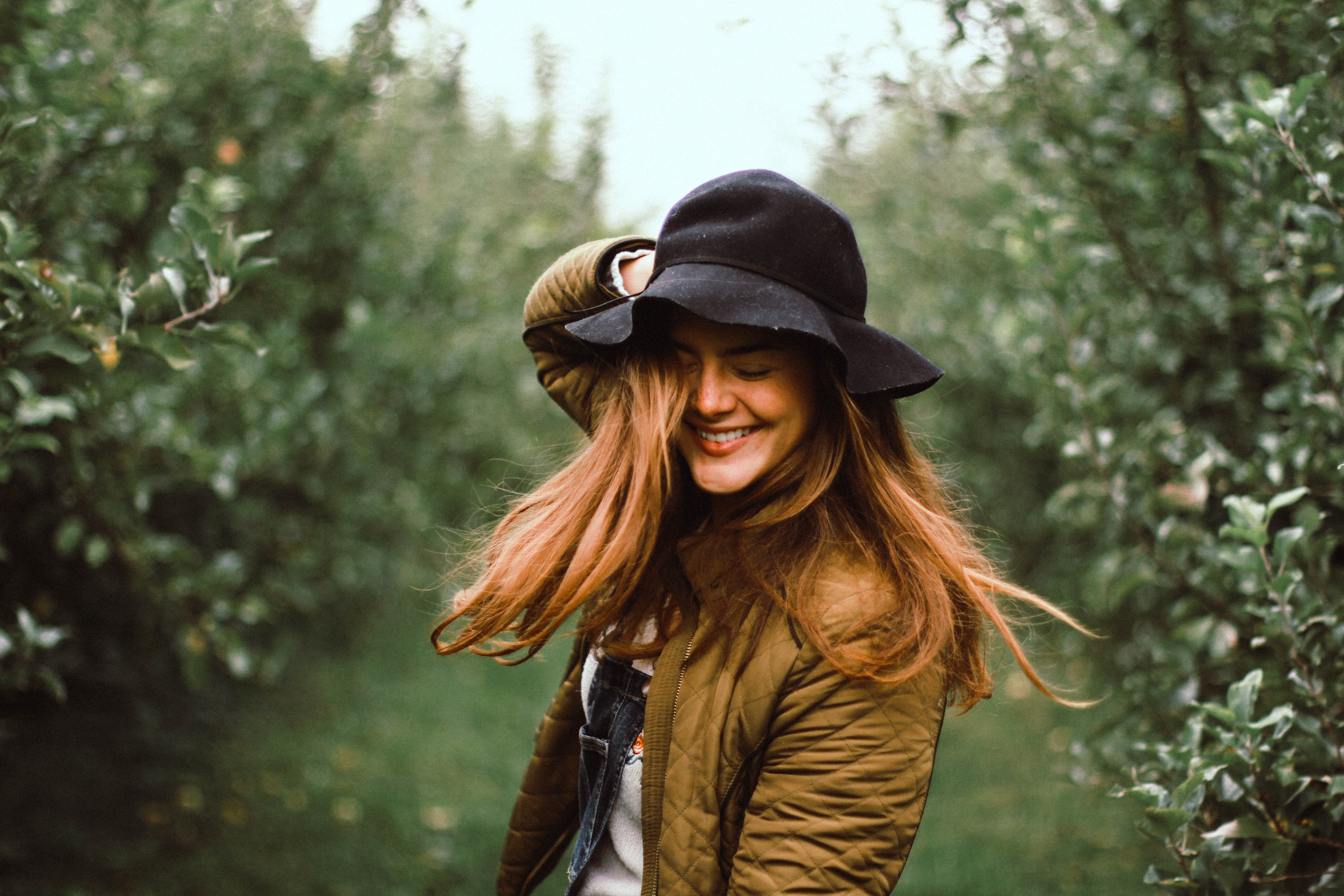 selective focus photography of woman holding her hat while smiling