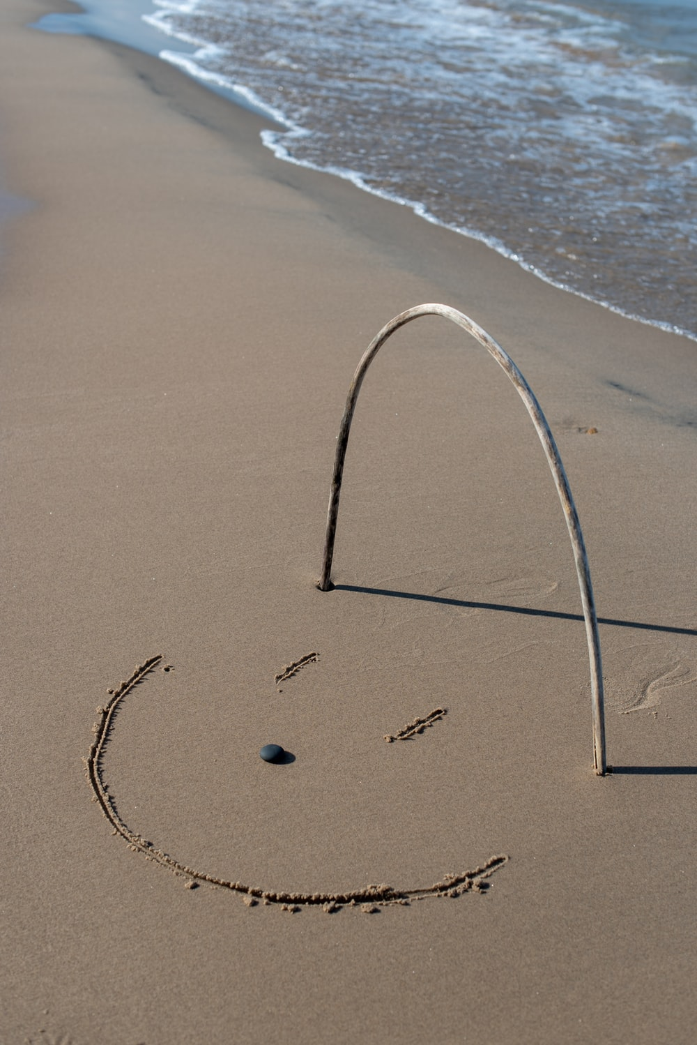 grey stick forming u letter on the seashore