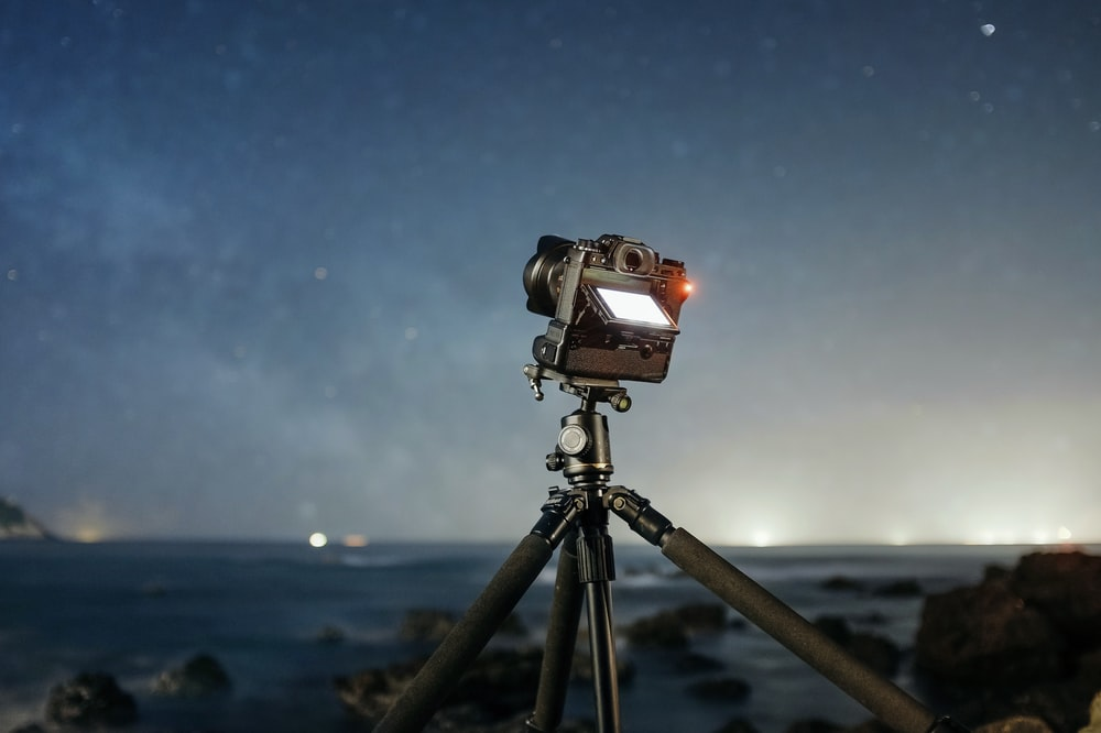 camera with tripod facing the stars during night time