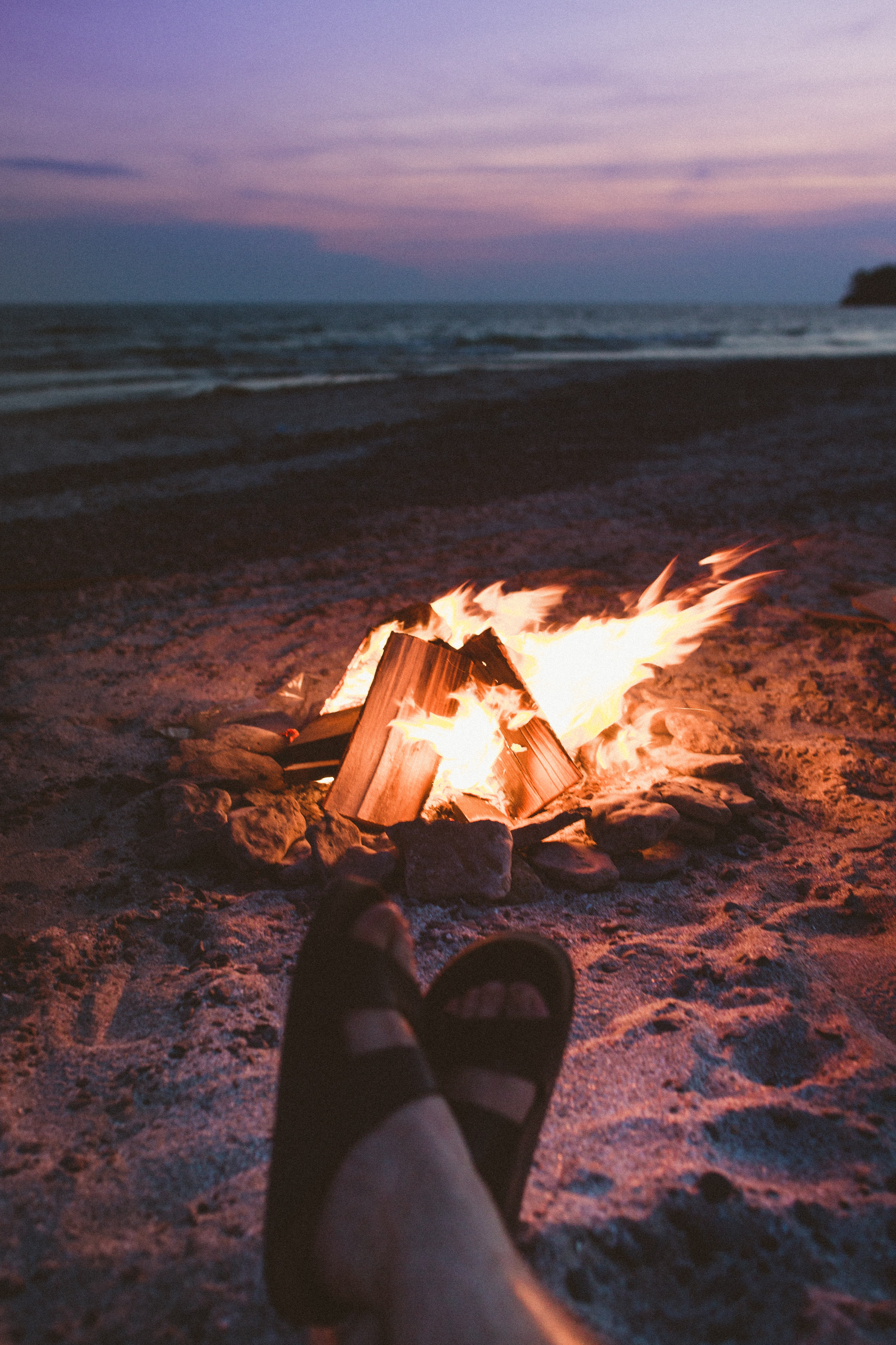 selective focus photography of person wearing black 2-strap slide sandals in front of burned bonfire on beach shore