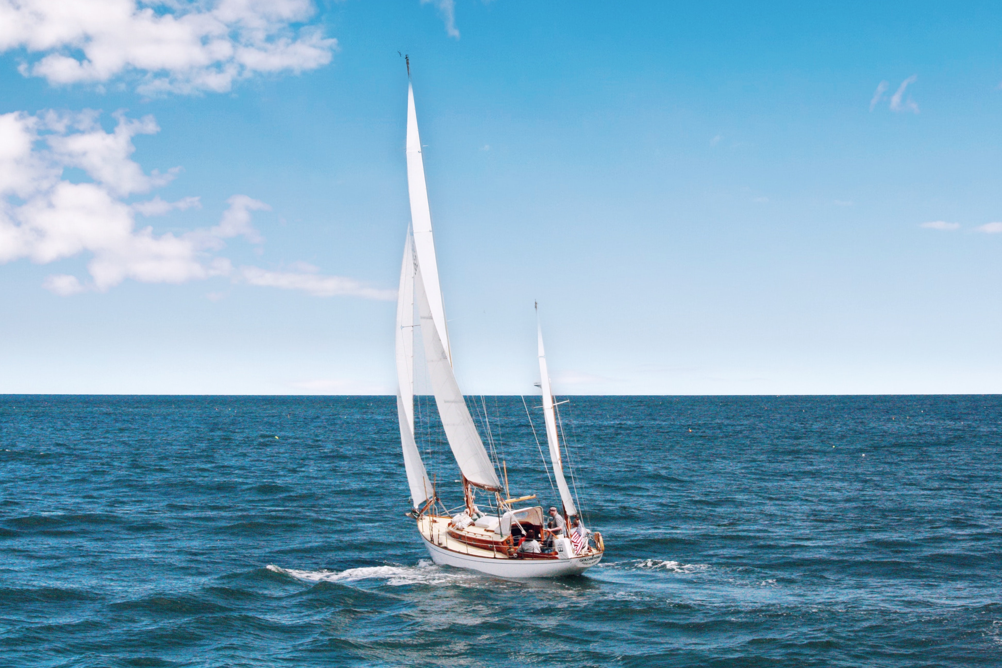 white sail boat on body of wate