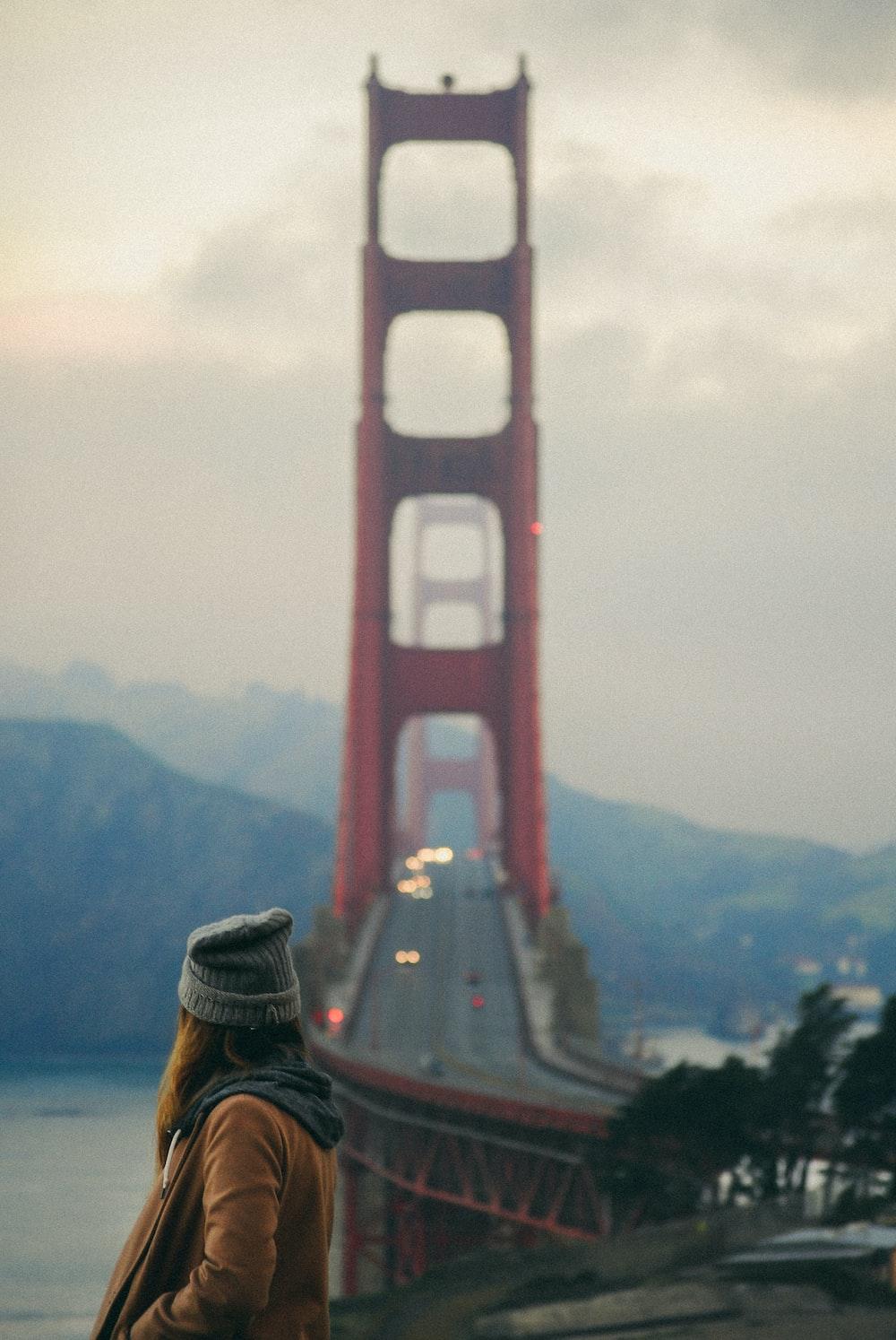 woman wearing grey beanie staring at Golden Gate Bridge