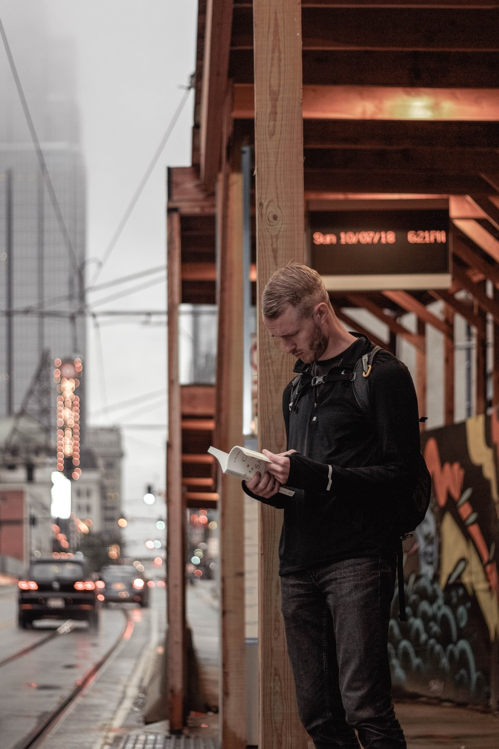 man in black sweater stands on sidewalk with book in hand