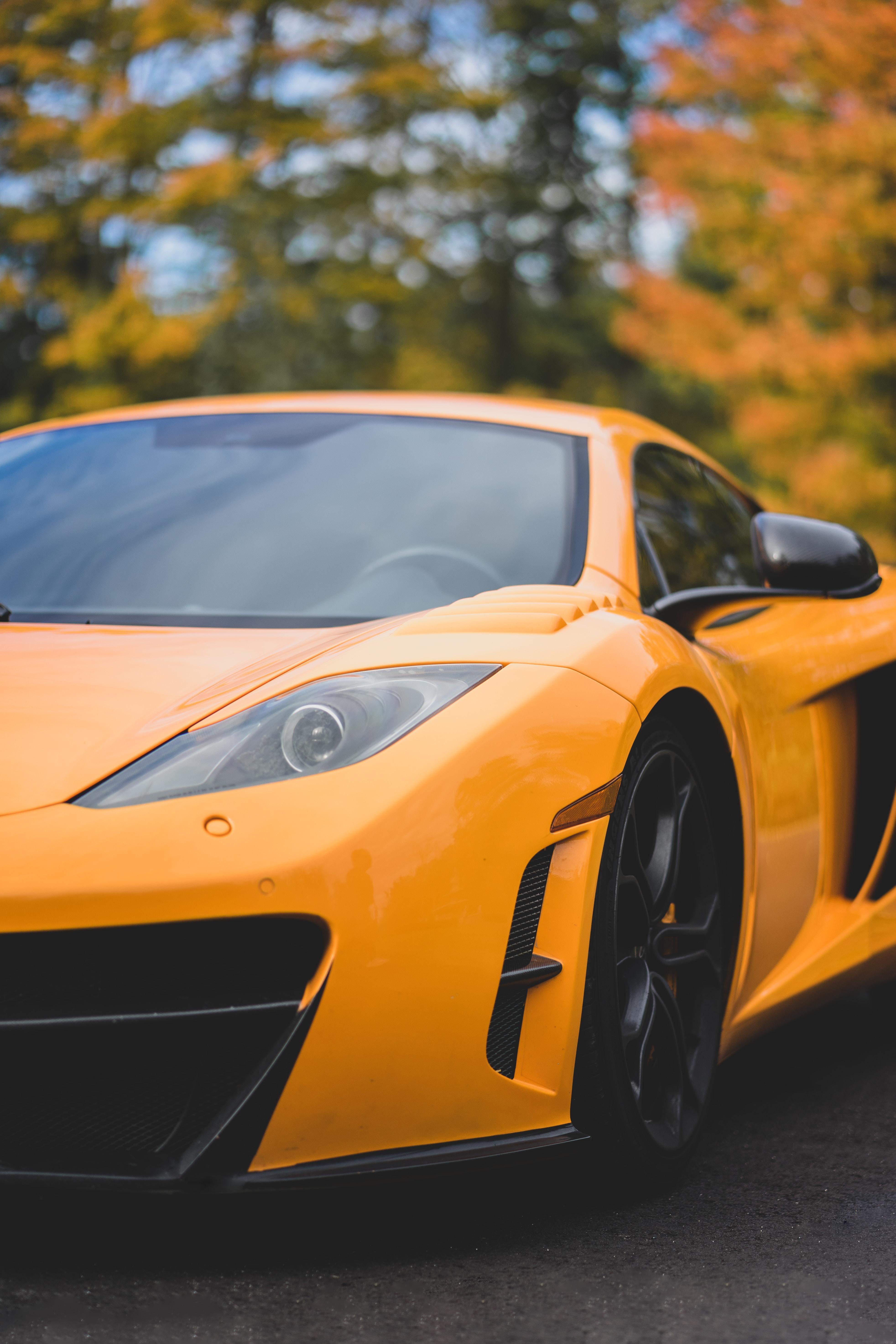 orange sports car near trees