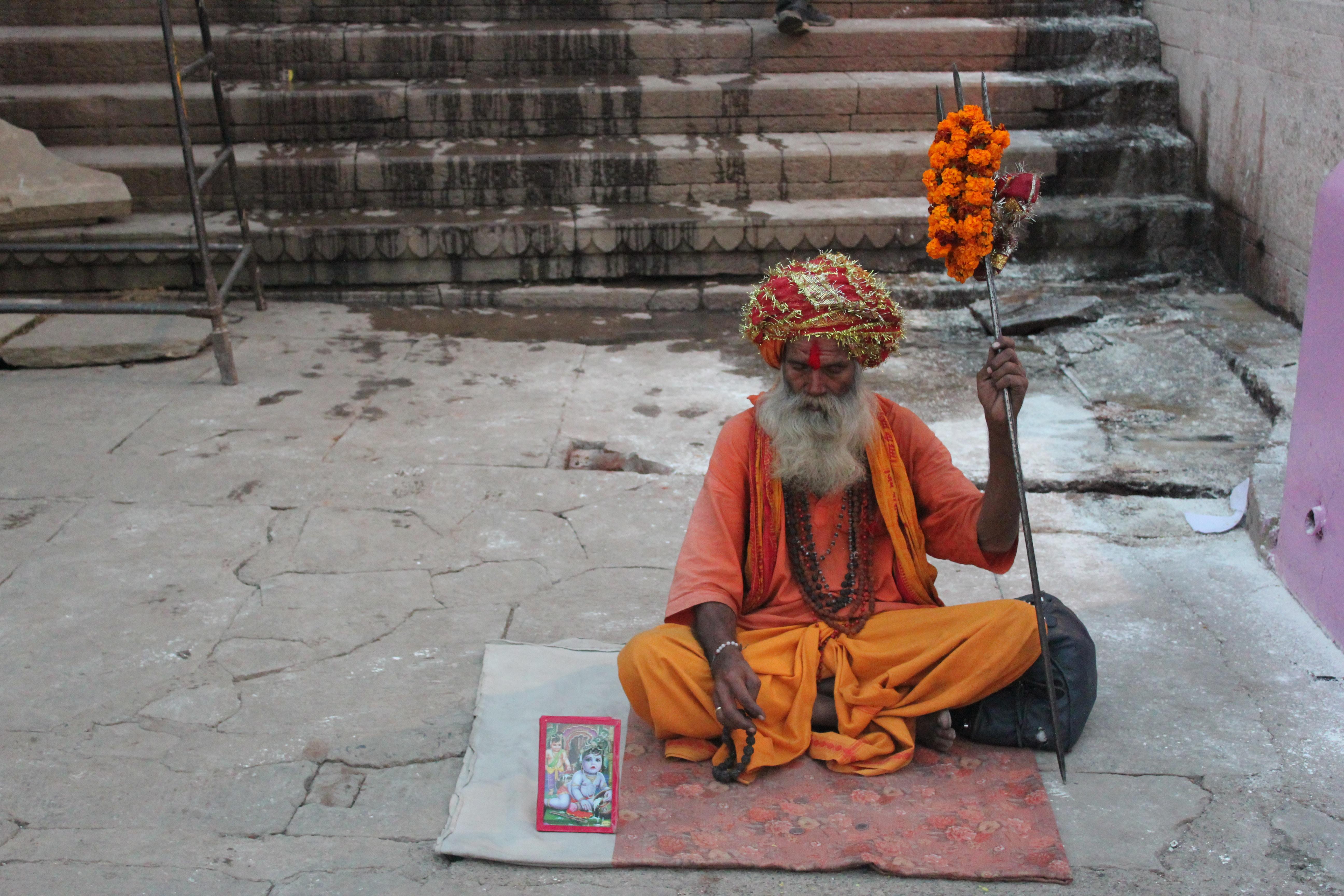 sitting man wearing orange and yellow elbow-sleeved shirt holding staff
