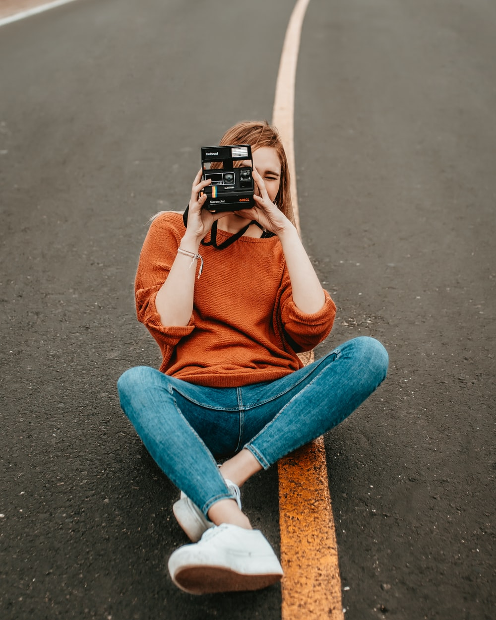 woman sitting at the middle of the road with one step camera during daytime