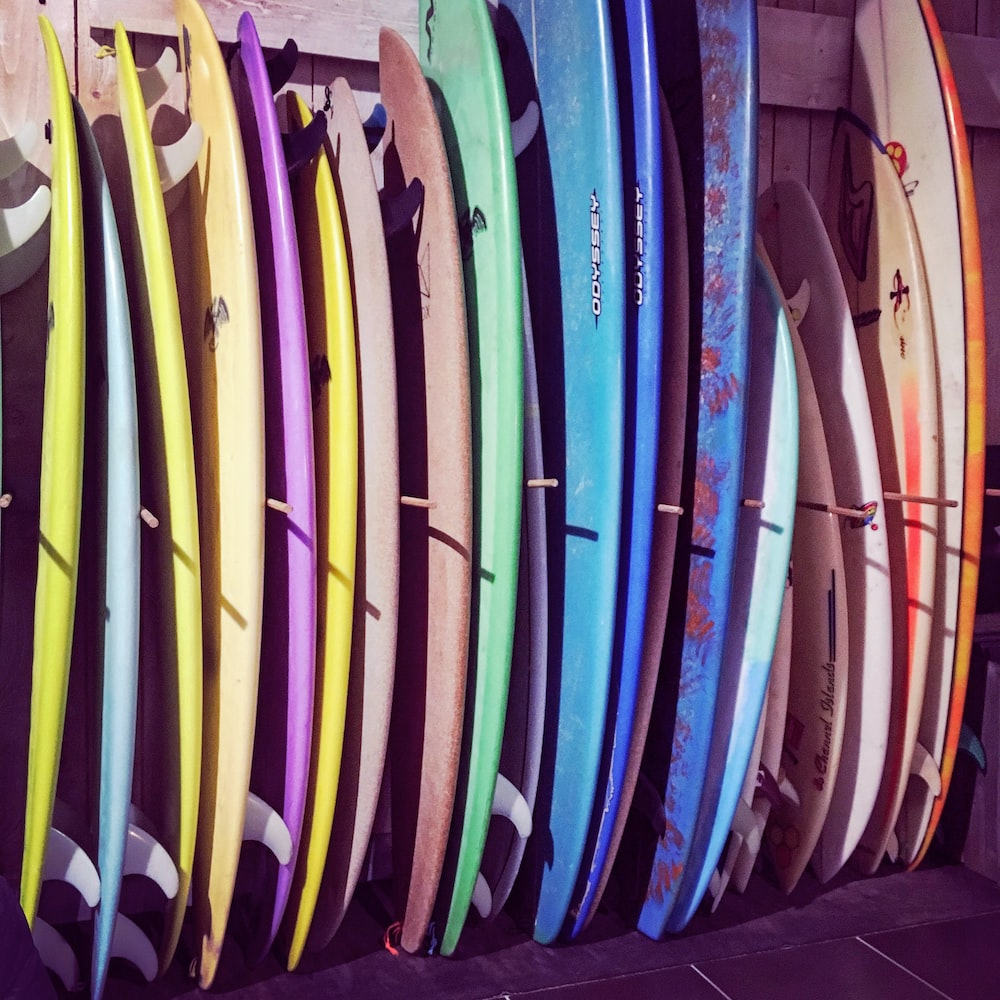 assorted color surfboards on rack