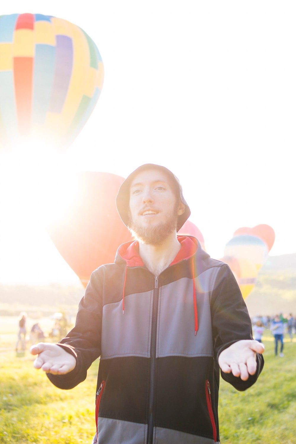 man wearing pullover hoodie standing near hot air balloons