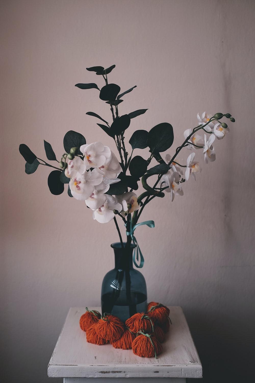 white flower bouquet inside blue glass vase