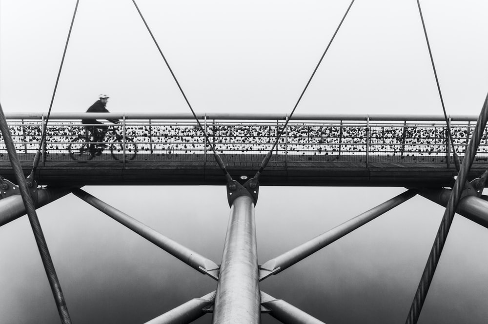 man cycling on suspension bridge