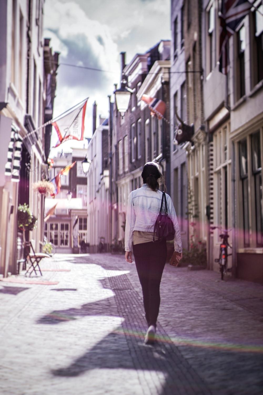 woman walking along buildings