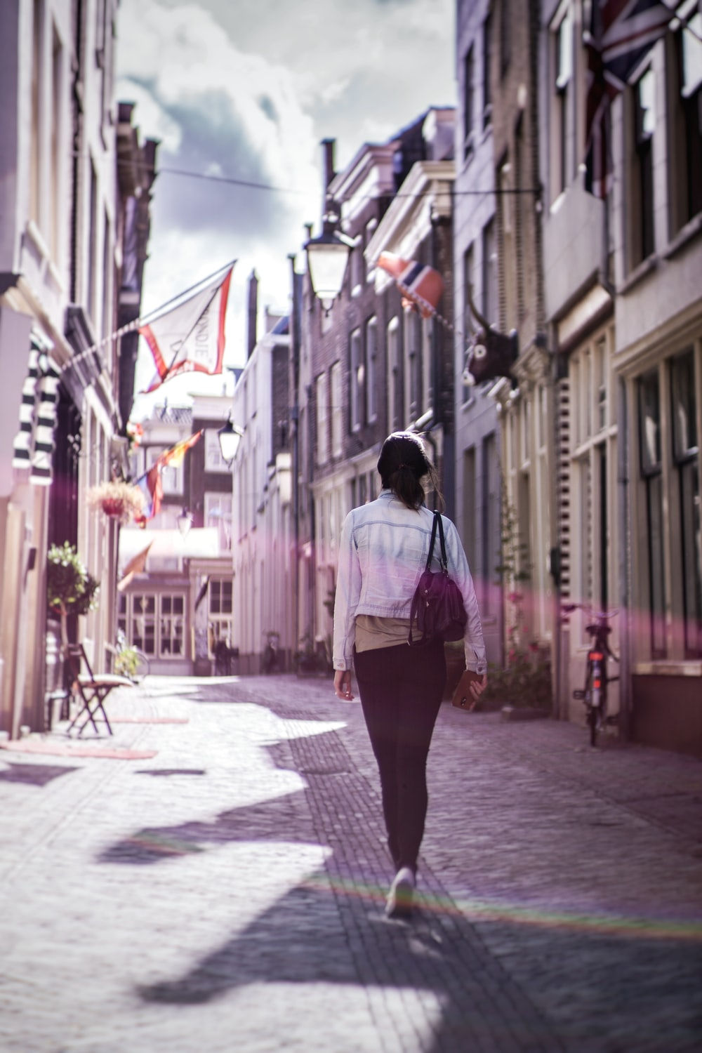woman walking along buildings