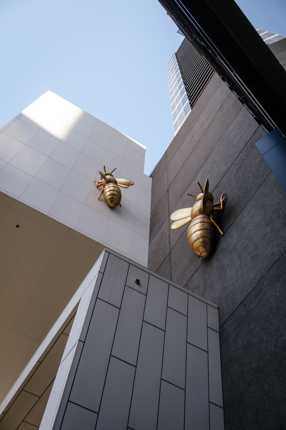 gray bees statuette on gray concrete buildings
