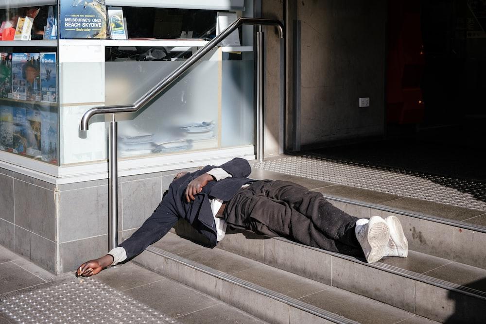 man wearing black blazer lying on gray stairs