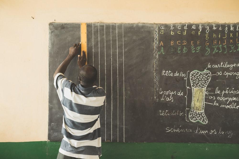 man writing on chalkboard