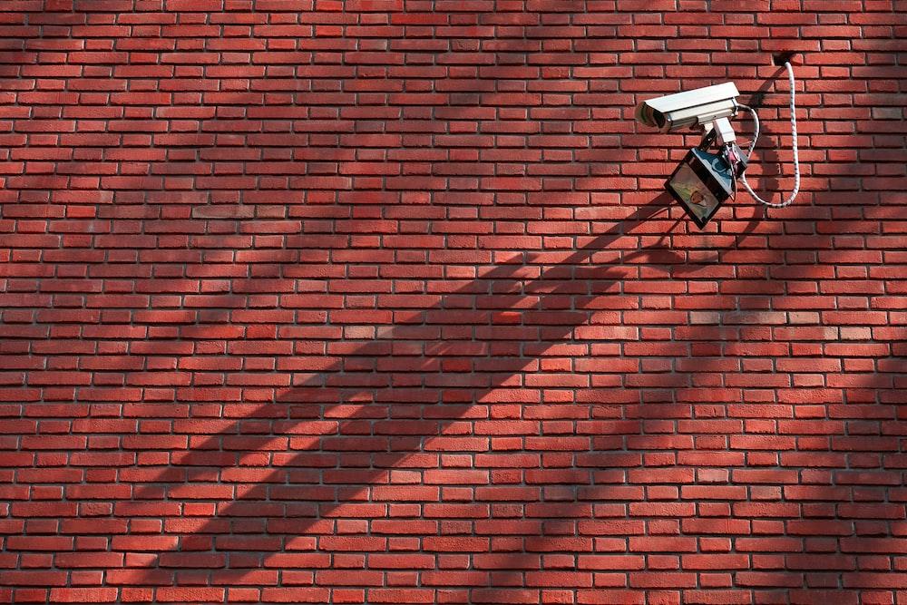 gray CCTV camera beside red bricked wall