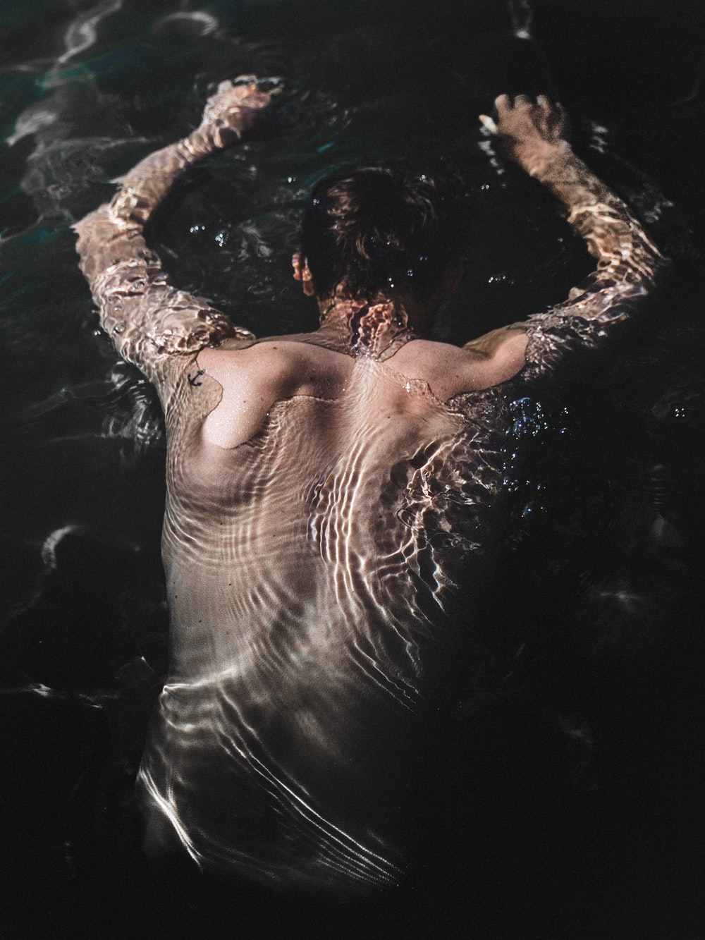 man floating at water during daytime