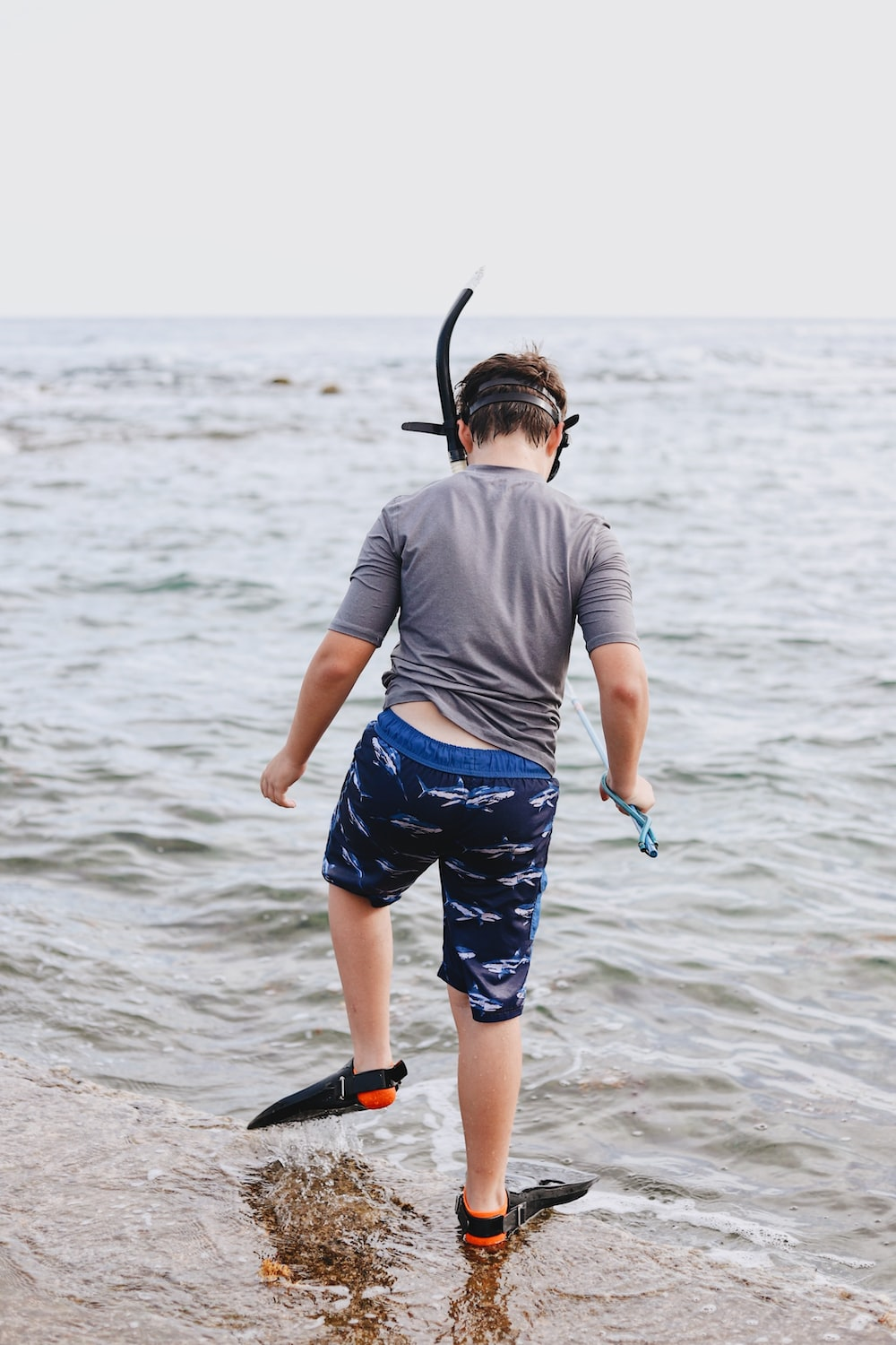 toddler standing outdoors near body of water