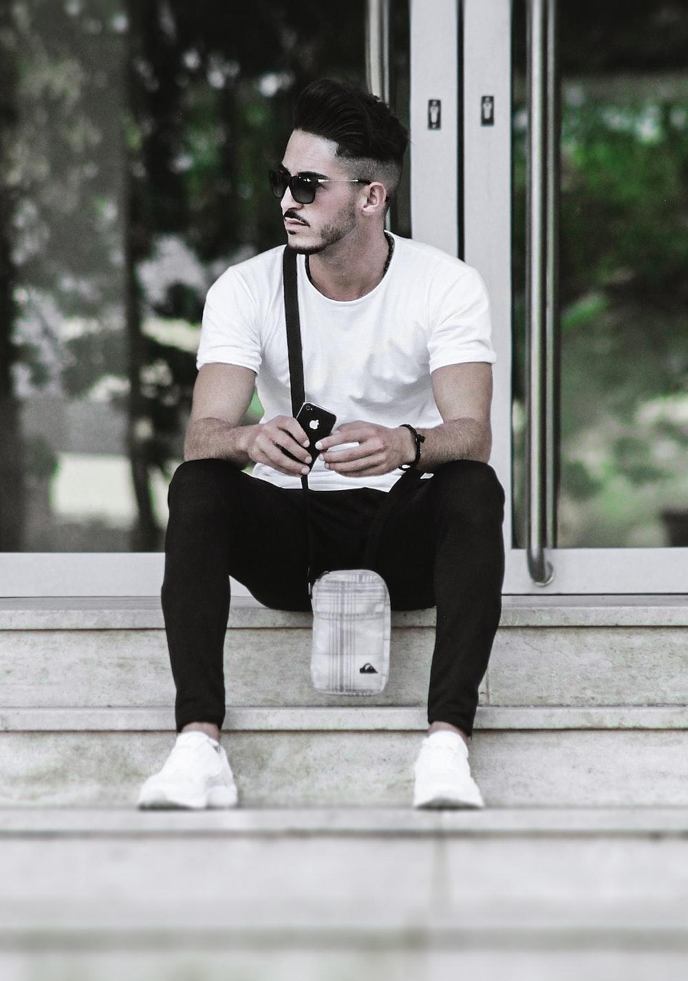 man wearing white shirt sitting on grey concrete stair case