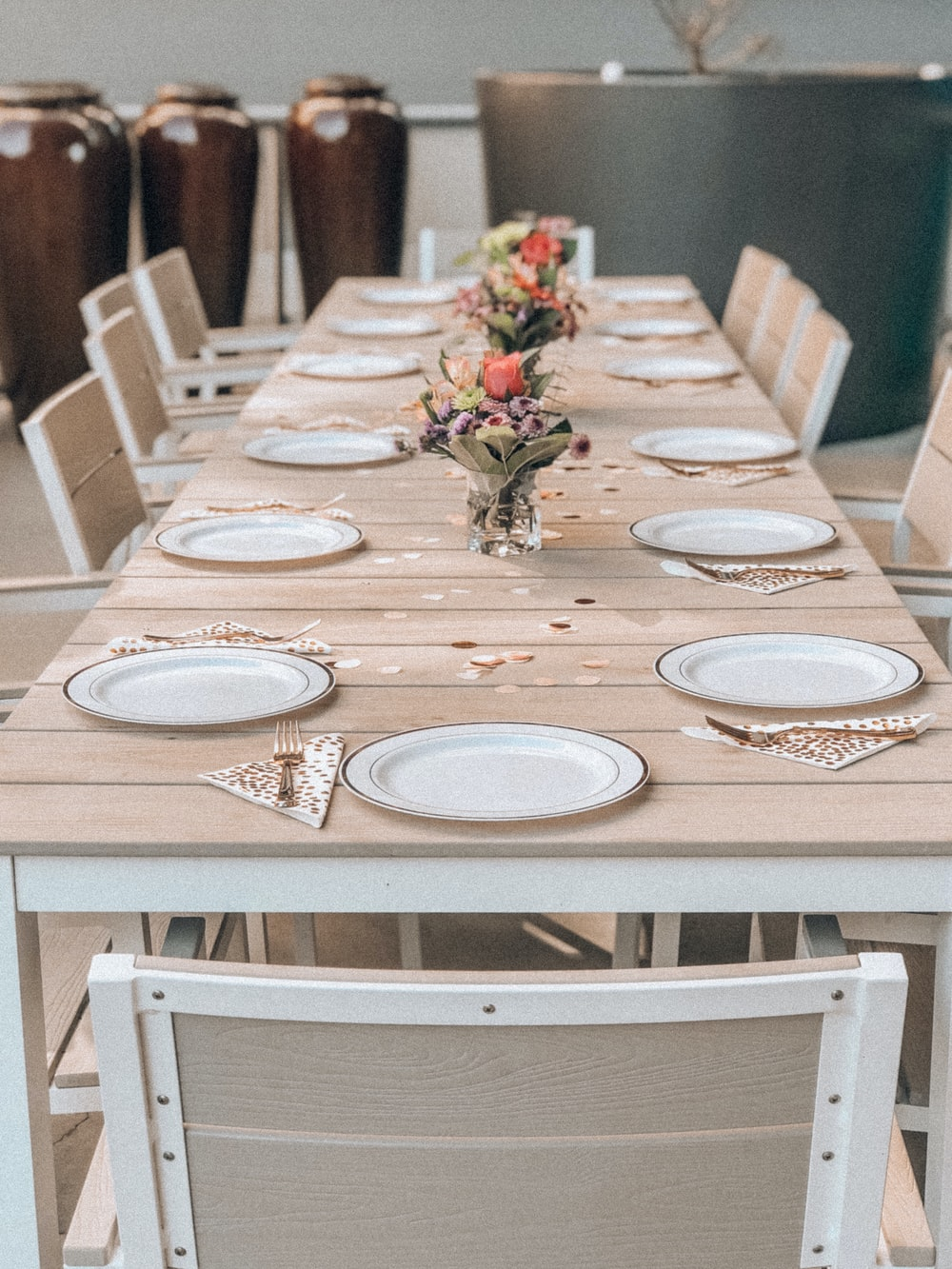 white ceramic plates on dining table with chairs