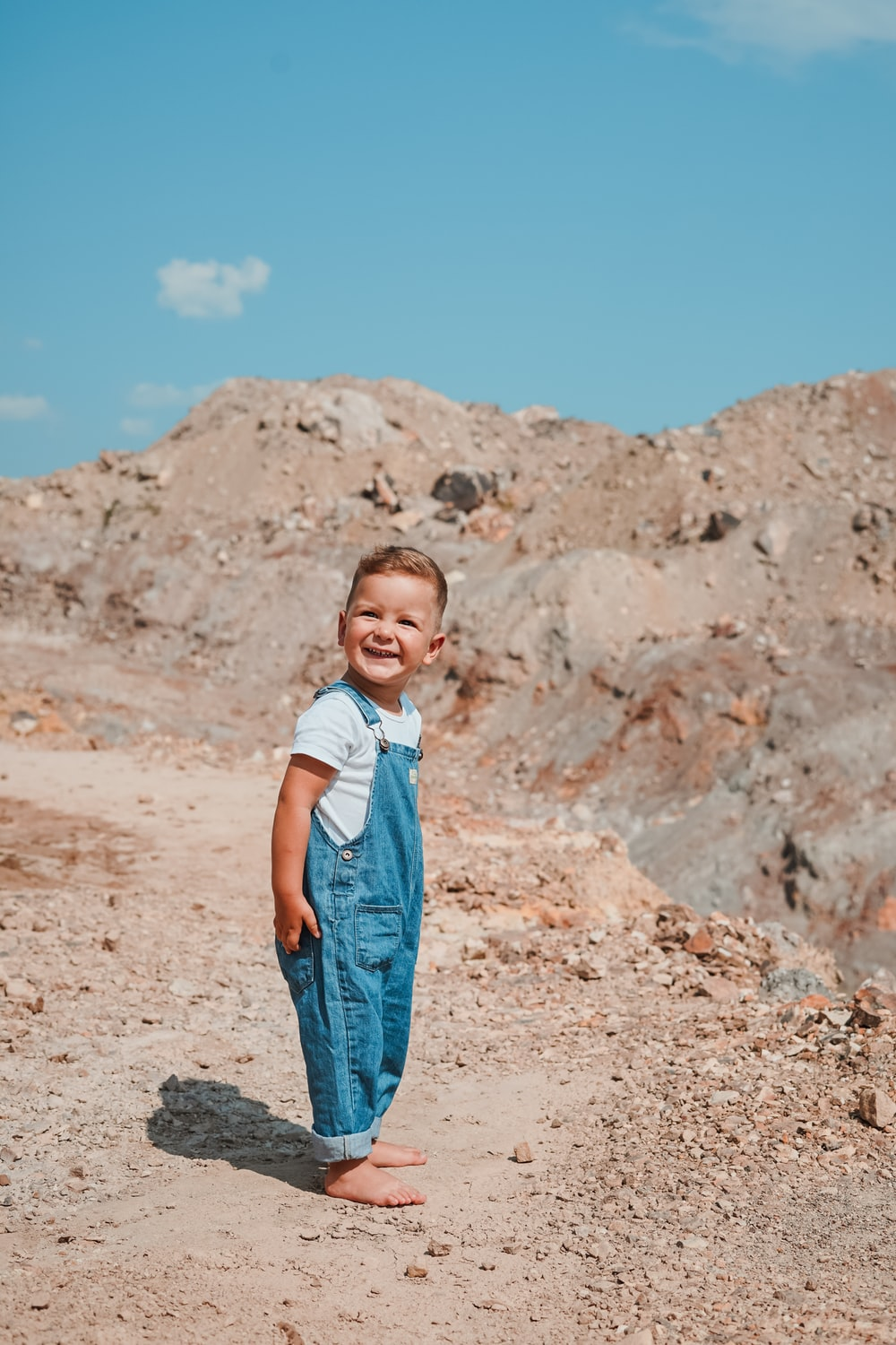 smiling boy standing near rock formations during daytime