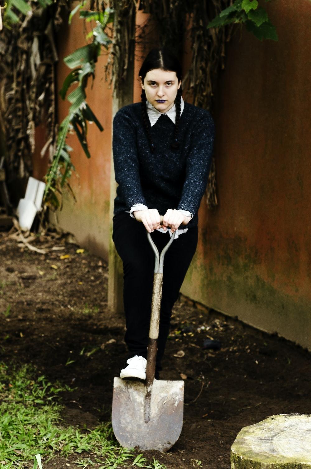 woman holding shovel near wall photo – Free Human Image on Unsplash