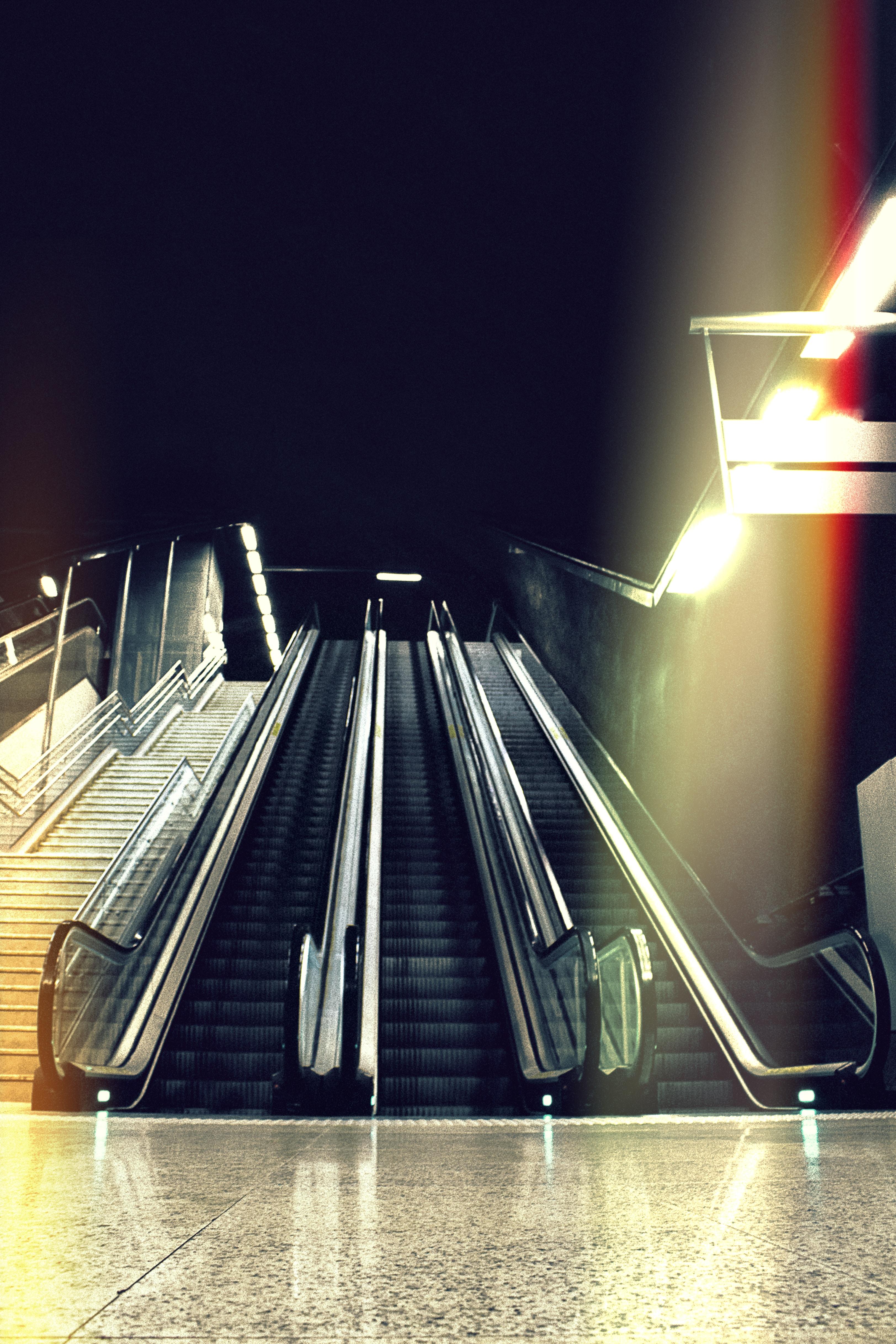black escalator beside stair