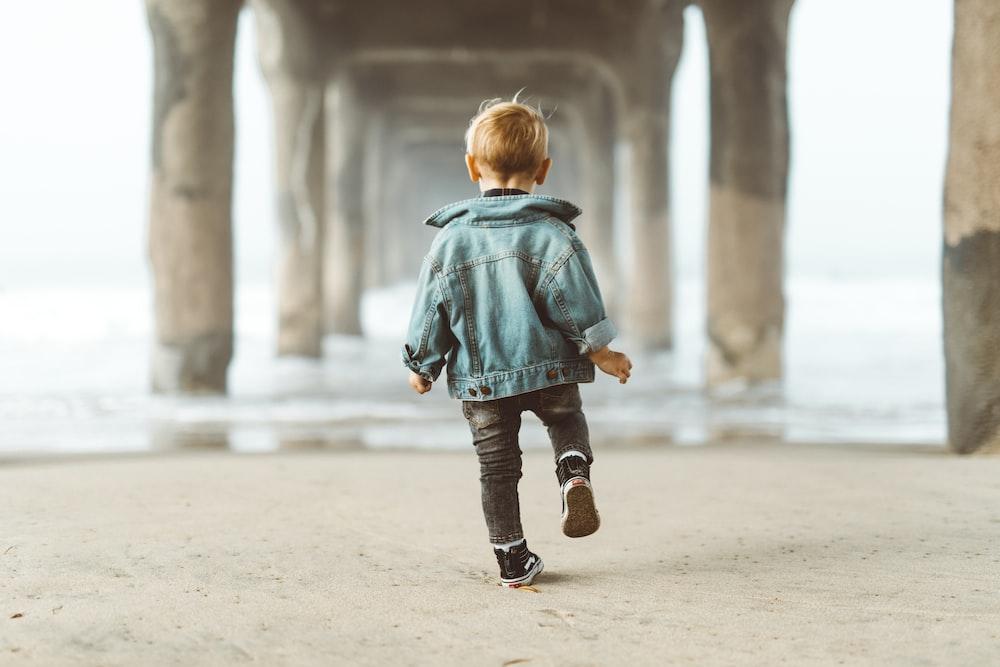 walking boy wearing blue denim jacket under the bridge