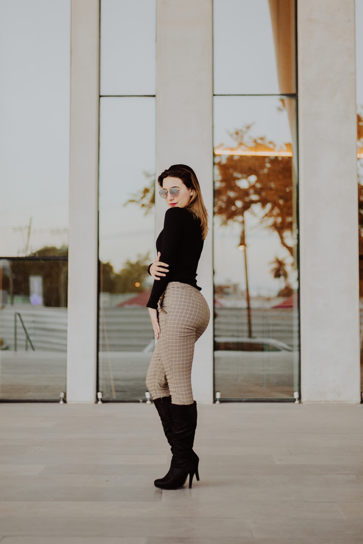 woman posing side ways near building