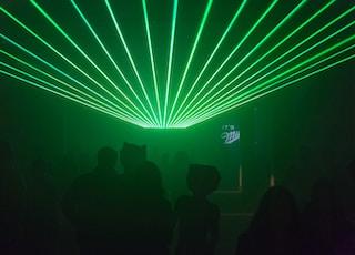 silhouette of people inside bar under green light