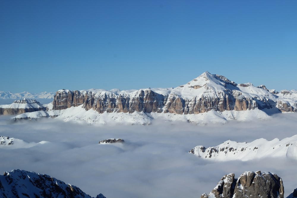 snow covered mountain above clouds under clear blue sky