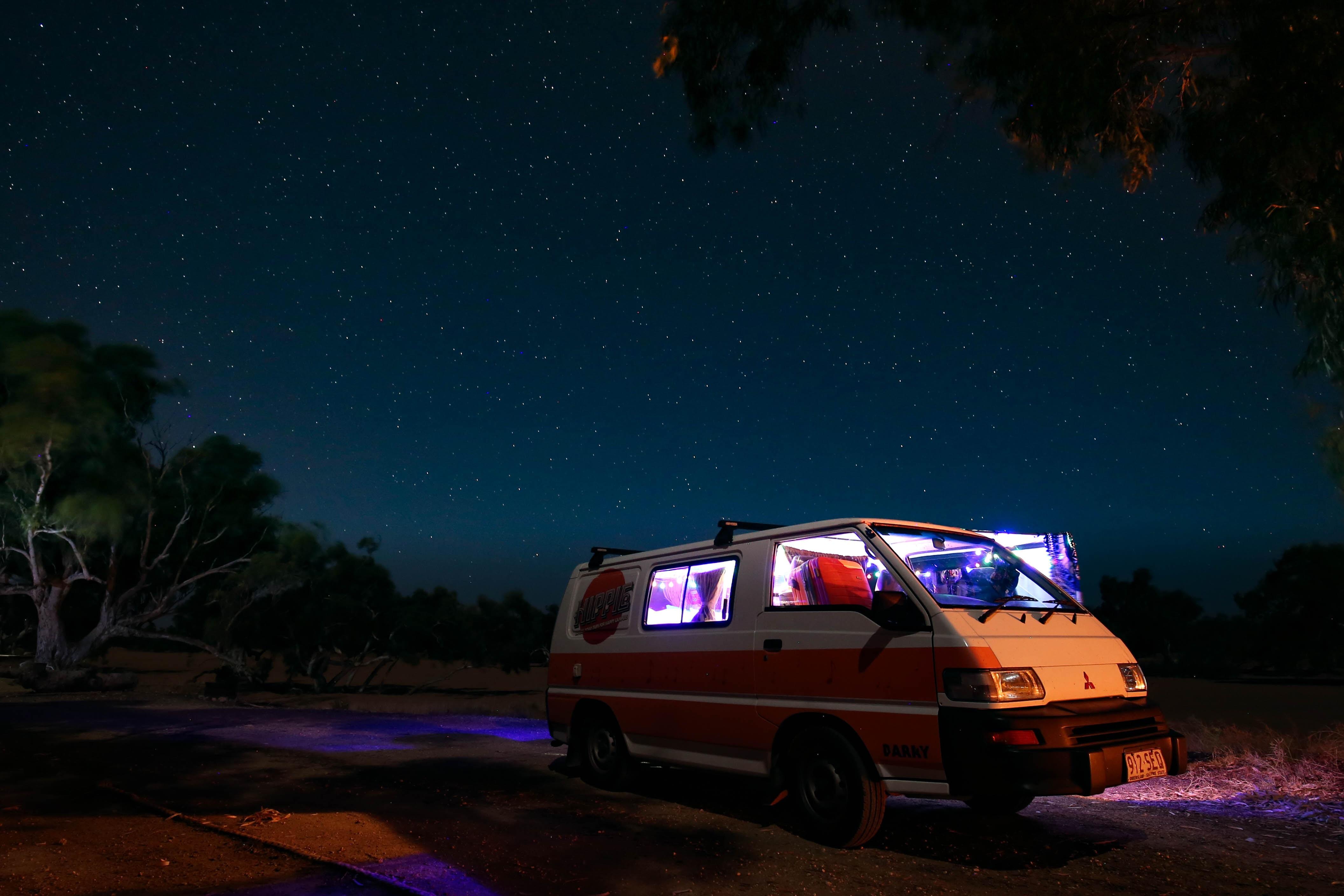 white Mitsubishi L300 parked near tree under starry sky