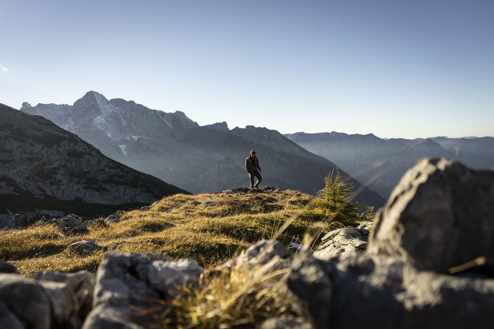 person standing on gray rocky mountain