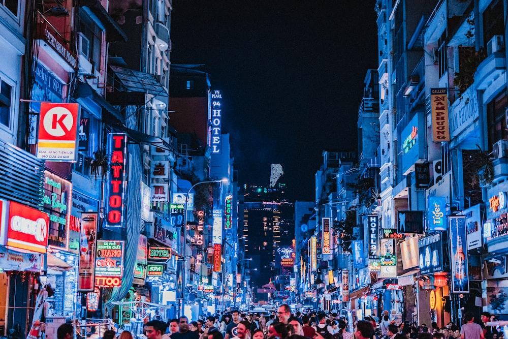 people between city buildings at night