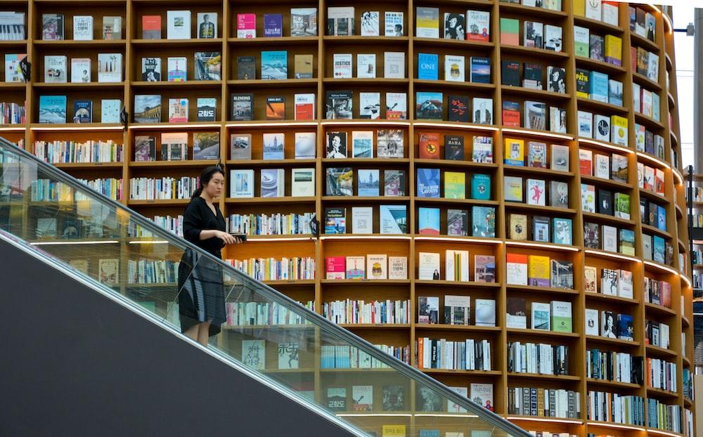 woman standing on escalator near brown wooden book shelves