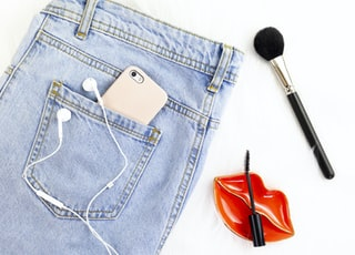 washed denim jeans and make-up brush