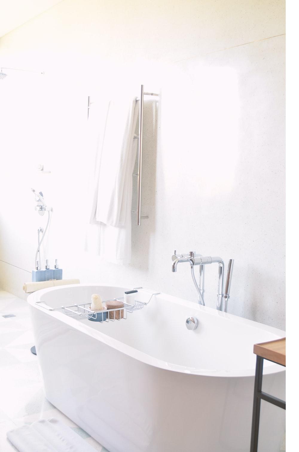 white drop-in bathtub near bath towel
