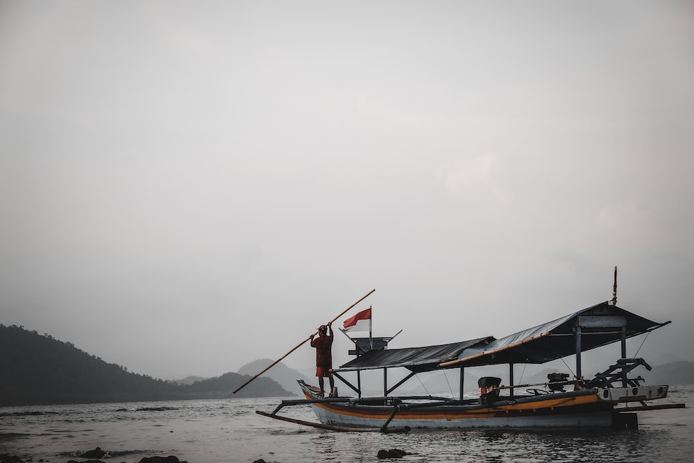 man standing on boat during foggy day