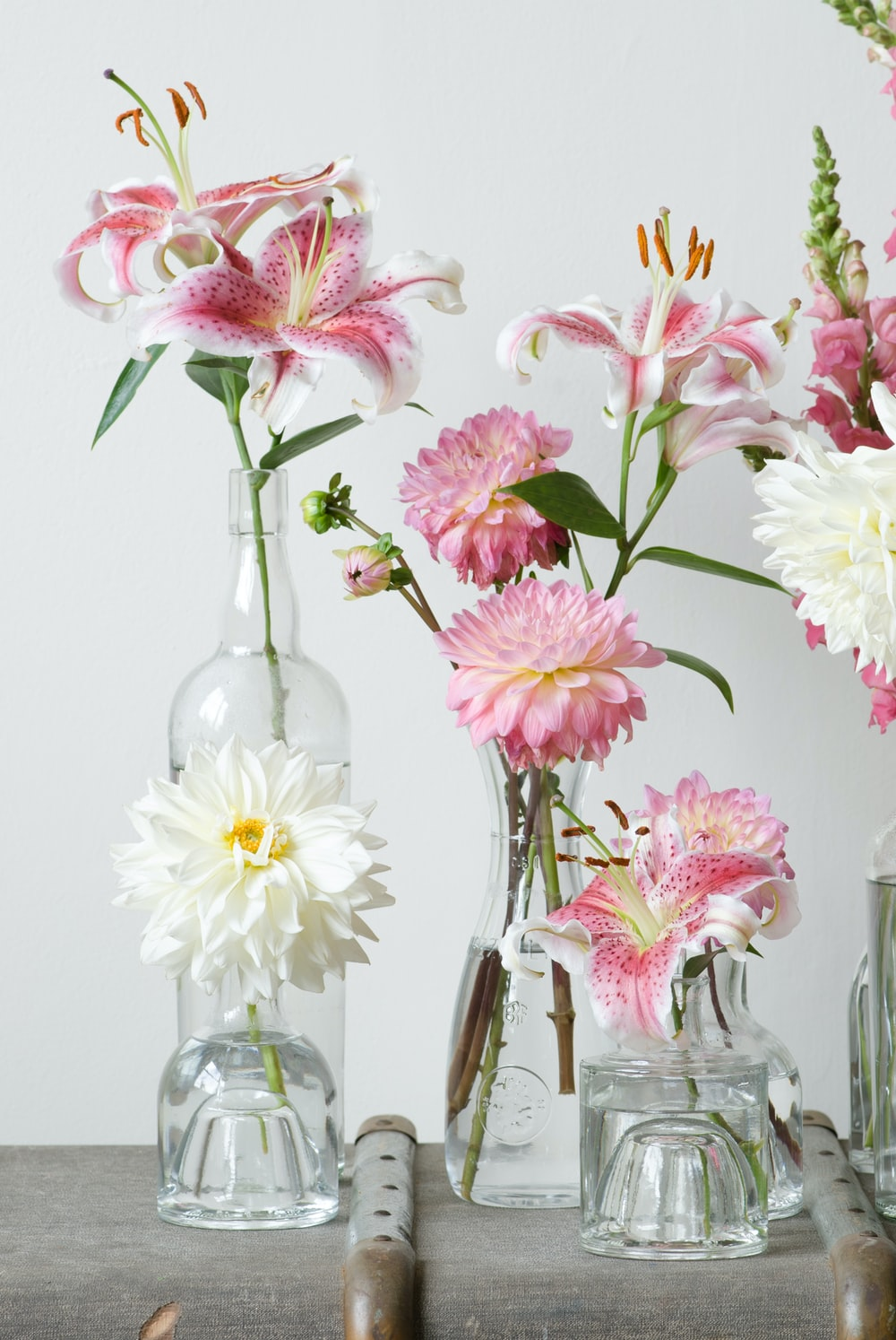 green-leafed plants with pink flowers in clear glass vase