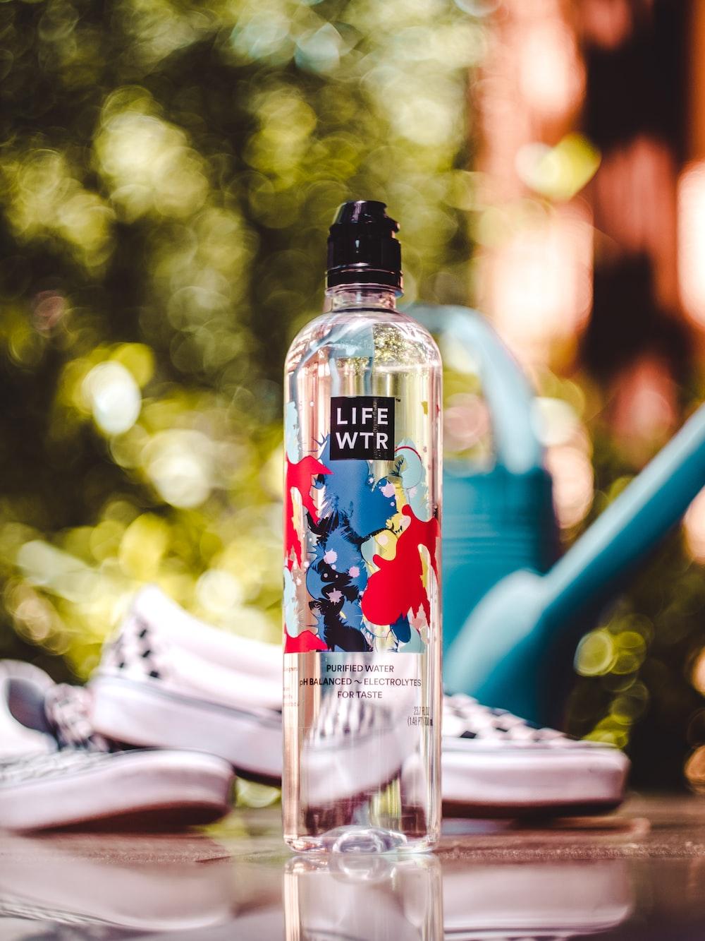 LIFE WTR bottle near black-and-white slip-on shoes