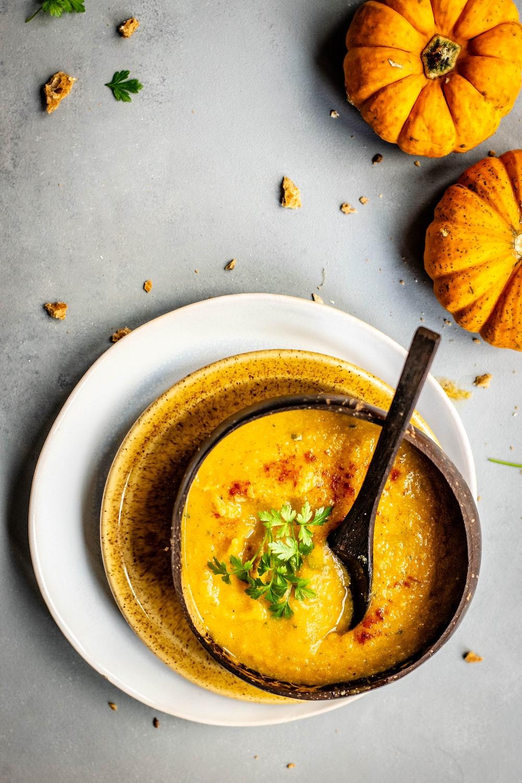 bowl of soup near two pumpkins