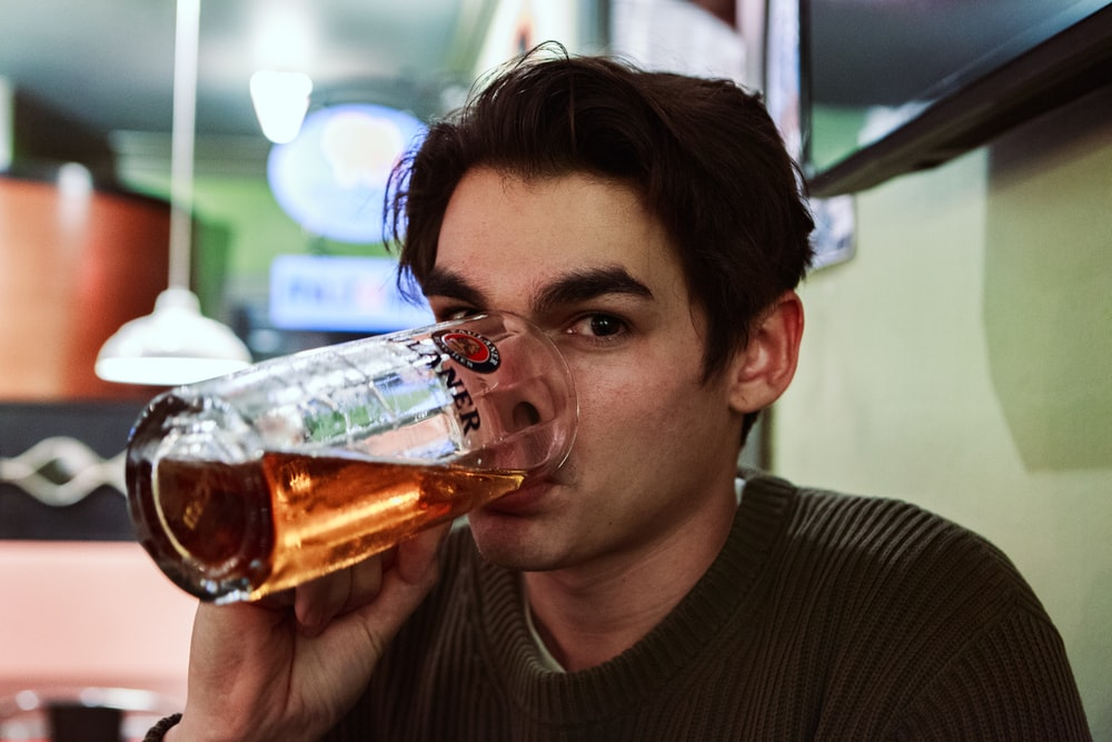 man drinking beer on selective focus photography