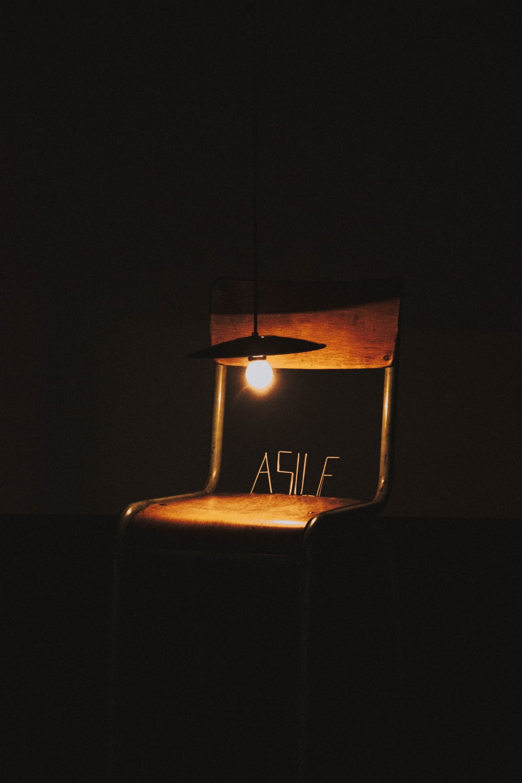black pendant lamp beside brown steel chair